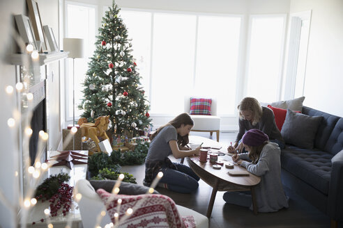 Mother and daughters making Christmas cards near Christmas tree in living room - HEROF20033