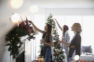 Mother and daughters decorating Christmas tree and hanging garland on fireplace mantle in living room - HEROF20039