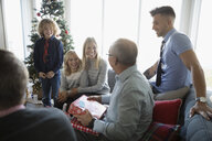 Multi-generation family watching grandfather opening Christmas gift in living room - HEROF20048