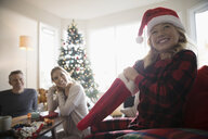 Parents watching happy daughter opening Christmas stocking in living room - HEROF20054