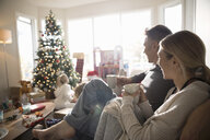 Parents drinking coffee, watching daughters opening Christmas gifts in living room - HEROF20057