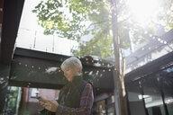 Senior woman texting with smart phone on sunny urban sidewalk - HEROF20084