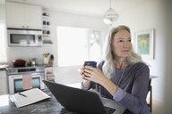 Senior woman drinking coffee at laptop in kitchen - HEROF20108