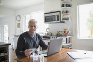 Senior man with credit card reordering prescription medication at laptop in kitchen - HEROF20126