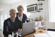 Senior couple paying bills at laptop at kitchen table - HEROF20129