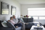 Senior couple relaxing, using digital tablet on living room sofa - HEROF20135