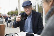 Senior man drinking coffee and talking to wife at sidewalk cafe - HEROF20147
