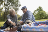 Senior couple playing chess on picnic blanket in park - HEROF20153