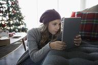 Serious teenage girl using digital tablet in living room with Christmas tree - HEROF20174