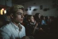 Serious tween boy watching movie in dark movie theater - HEROF20180