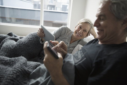 Senior couple relaxing, using digital tablet and smart phone in bed - HEROF20201