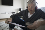 Senior man with headphones online shopping with digital tablet and credit card - HEROF20219