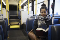 Woman commuter reading book on bus - HEROF20258