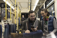Young couple commuters texting with smart phone on bus - HEROF20264