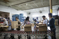 Volunteers filling donation boxes in warehouse - HEROF20288