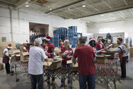 Volunteers in Santa hats filling Christmas donation boxes in warehouse - HEROF20294
