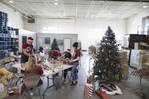 Volunteers wrapping Christmas gifts in warehouse - HEROF20297