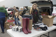 Young female volunteer sorting and loading donations in parking lot - HEROF20300