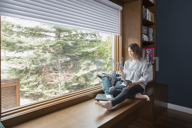 Woman texting with smart phone at window seat in home office - HEROF20327 - Hero Images/Westend61