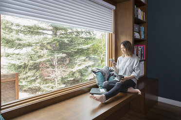 Woman texting with smart phone at window seat in home office - HEROF20327