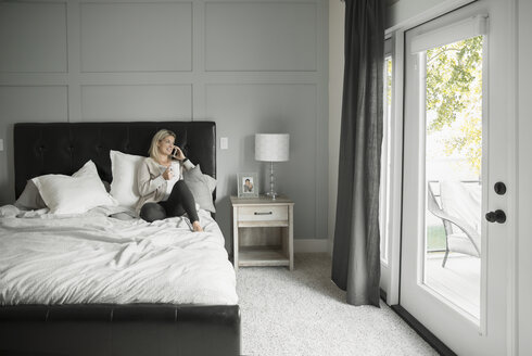 Thoughtful woman relaxing, drinking coffee and talking on cell phone in bed - HEROF20348