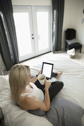 Woman relaxing, drinking coffee and using digital tablet on bed - HEROF20354