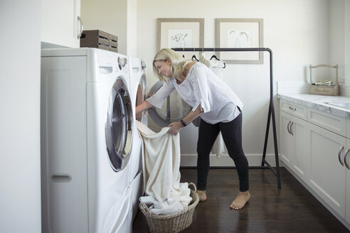 Woman removing laundry from dryer in laundry room - HEROF20357