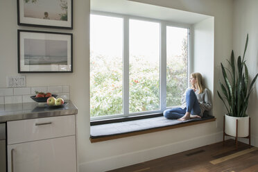 Thoughtful woman relaxing at window seat, looking out window - HEROF20366