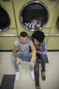 Young couple using digital tablet, waiting for laundry at laundromat - HEROF20387