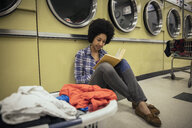 Young woman reading book, waiting for laundry at laundromat - HEROF20390