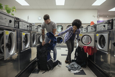 Young couple backpackers doing laundry at laundromat - HEROF20393