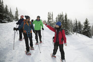 Woman leading snowshoeing tour for group of friends in snow - HEROF20420