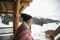 Young woman enjoying snowy view from ski resort lodge balcony - HEROF20423