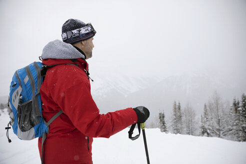 Thoughtful male skier enjoying snowy mountain view - HEROF20444