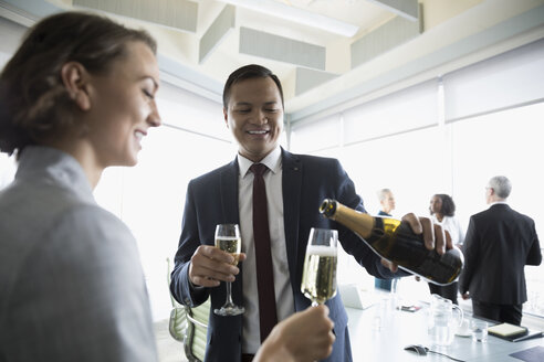 Happy businessman celebrating, pouring champagne for businesswoman in conference room - HEROF20465
