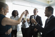 Happy business people celebrating, toasting champagne glasses in conference room - HEROF20468