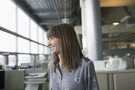 Happy, confident businesswoman looking away in office - HEROF20483