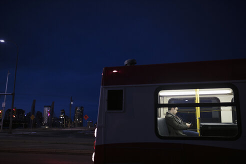 Male commuter riding bus at night - HEROF20486