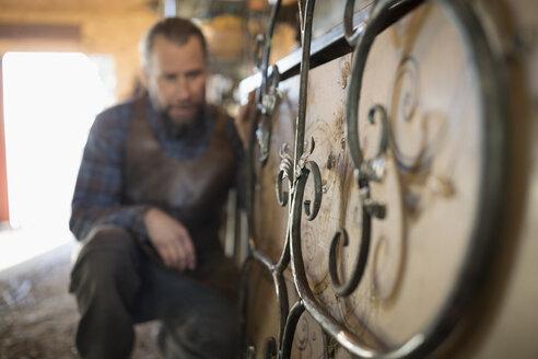 Male blacksmith examining scrolled metal - HEROF20507