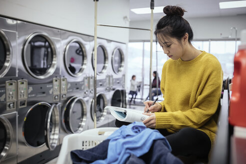 Focused female college student studying, waiting for laundry at laundromat - HEROF20552