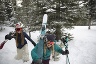 Happy female skier friends hiking remote snow - HEROF20585
