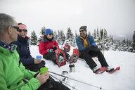 Friends enjoying coffee, taking a break from snowshoeing in snow - HEROF20606