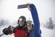Happy, affectionate couple skiers taking selfie with camera phone - HEROF20639