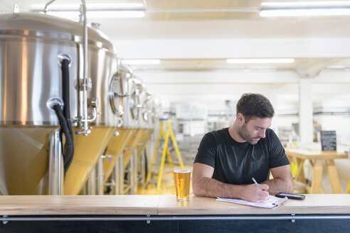 Brewer ordering ingredients on phone in small brewery - CUF48540