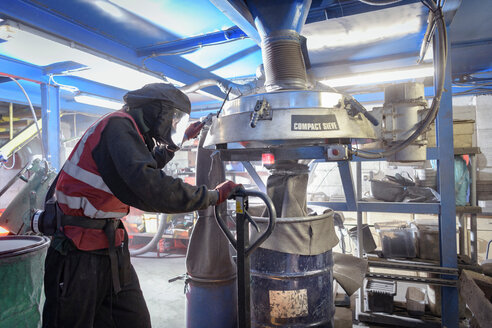 Worker sieving recycled metals from catalytic converters in recycling factory - CUF48555