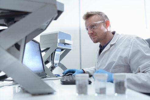 Worker inspecting samples in laboratory in recycling factory - CUF48558