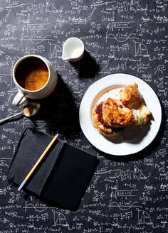 Coffee, breakfast biscuit with raspberry jam on blackboard background , overhead view - CUF48639