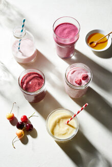 Fruit and yogurt smoothies in glass bottle and jars, overhead view - CUF48642