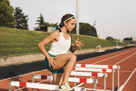 Female athlete doing warm-up exercises on tartan track - ACPF00445