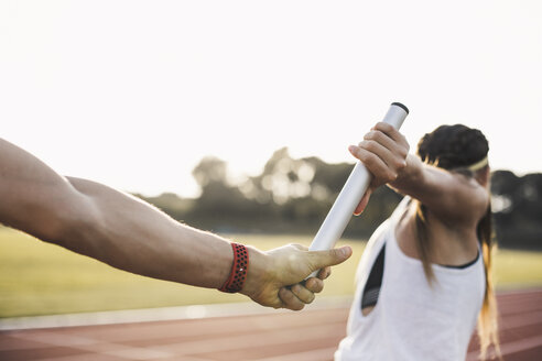 Close-up of a athlete passing the baton to a female athlete - ACPF00451